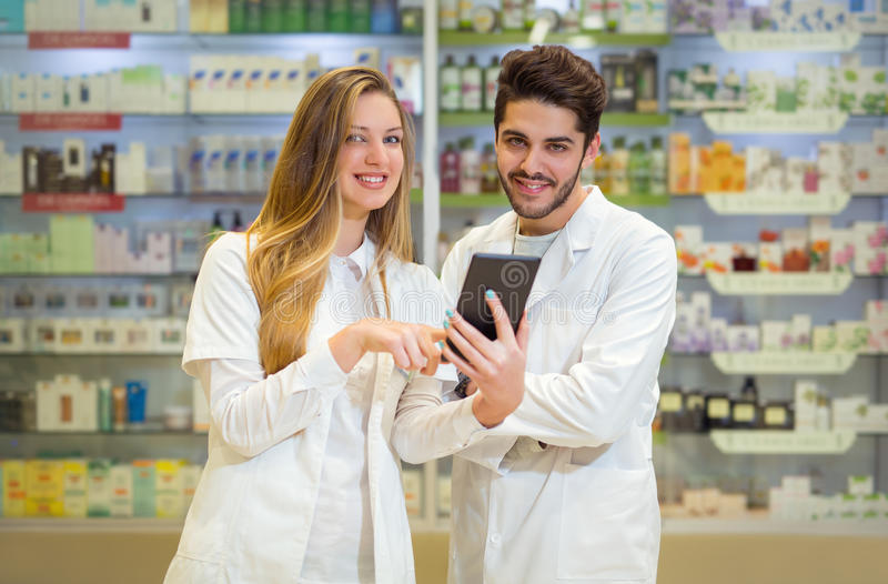 Pharmacists using digital tablet while checking medicine. In pharmacy royalty free stock photos
