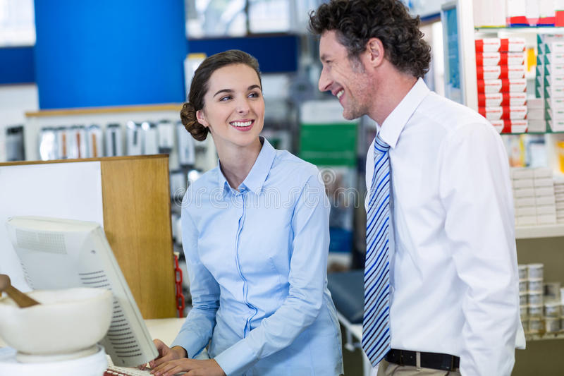 Pharmacists working on computer in pharmacy stock photography