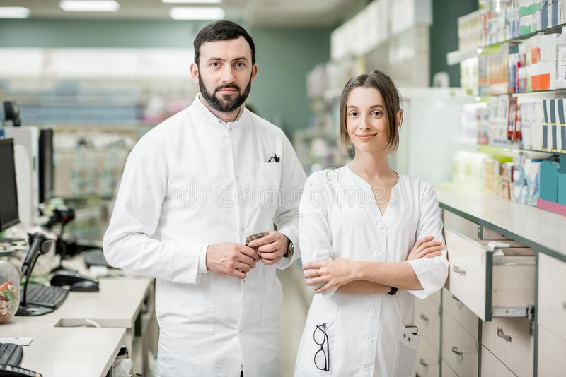 Pharmacists working in the pharmacy store. Portrait of a two pharmacists standing at the paydesk selling medications in the pharmacy store stock photos