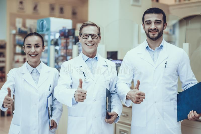 Pharmacists working in pharmacy. Three Pharmacists Posing. Pharmacists is a Caucasian Men and Young Woman. Persons Showing OK Sign. People Wearing a Special royalty free stock photos