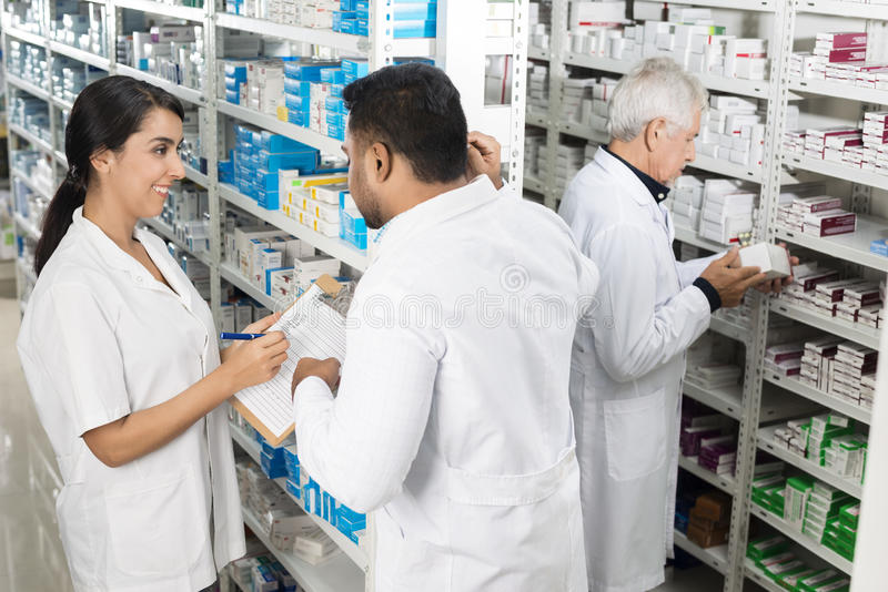Pharmacists Working By Shelves In Pharmacy royalty free stock photography