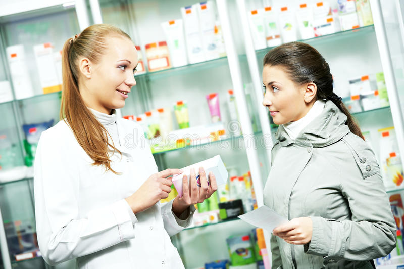 Pharmacy chemist consulting woman in drugstore stock photo