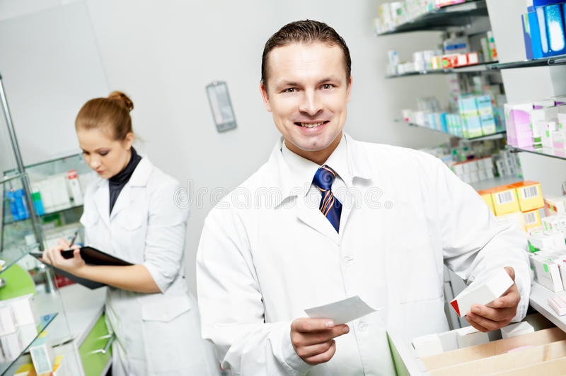 Pharmacy chemist man in drugstore stock image