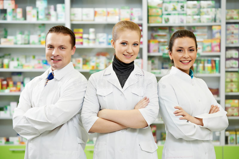 Pharmacy chemist team women and man in drugstore stock image