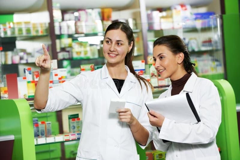 Pharmacy chemist women in drugstore stock images