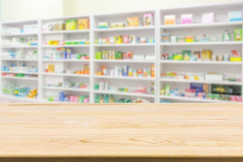Pharmacy drugstore counter table with blur abstract backbround. With medicine and healthcare product on shelves royalty free stock photography