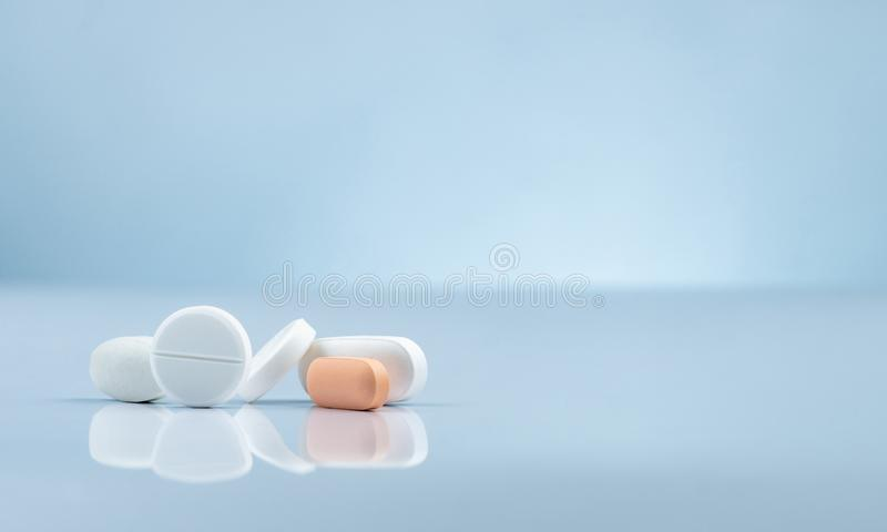 Pharmacy drugstore product. Pile of orange and white tablets pill on gradient background. Different size and shape tablets pills. Pharmaceutical industry royalty free stock photo