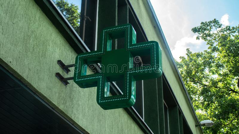 Pharmacy green cross sign led. Pharmacy green cross sign with led light on the wall exterior single object sunny weather royalty free stock photography