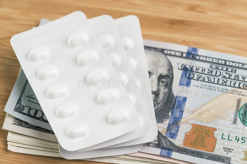 Pharmacy, health care or medical expense concept, white package of pills on pile of US dollar banknotes money stock image