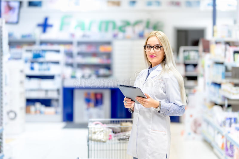 Pharmacy scientist using tablet in pharmaceutical field. medical details with blonde pharmacist stock photo