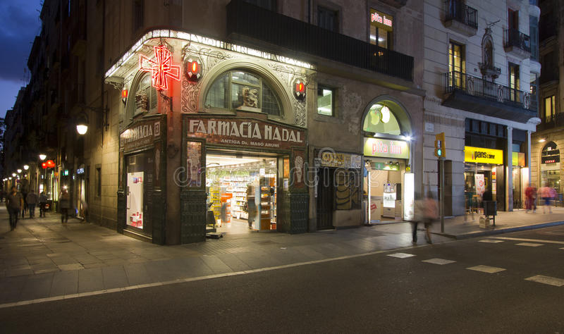 Pharmacy Shop in Barcelona. Barcelona, Spain - May 26, 2015: Pharmacy shop and people walking in the evening on Ramblas street in Barcelona, on May 26, 2015 in royalty free stock image