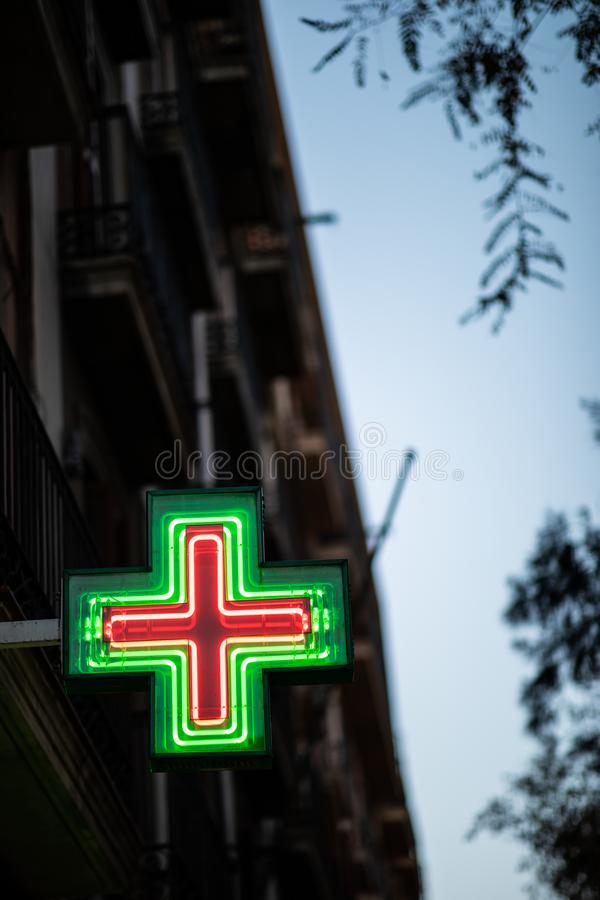 Pharmacy sign illuminated at night on spanish architecture facade. With copy space, spain, health, urban, city, pomegranate, isolated, medicine, assisted stock photo
