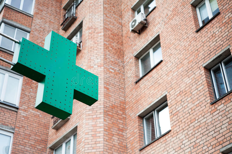 Pharmacy sign on the street. Green pharmacy cross on a background of the building royalty free stock image
