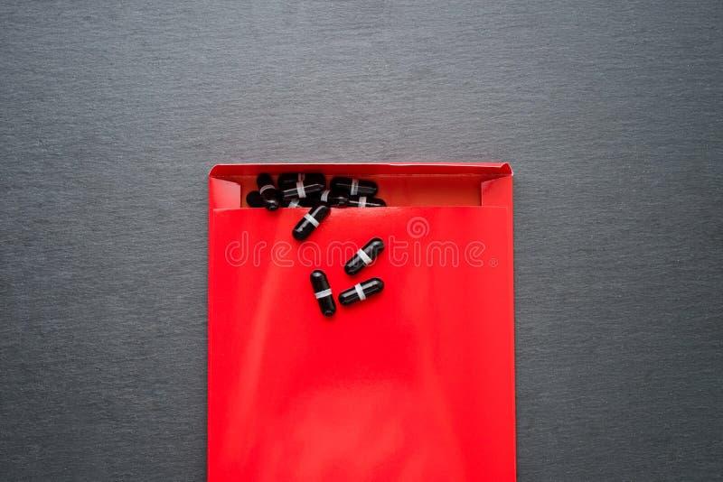 Pharmazeutische Medizin und Ergänzung mit schwarzen Kapseln im Paket Ärztliche Behandlung, die Tätigkeit hilft, Unterstützung für stockfoto