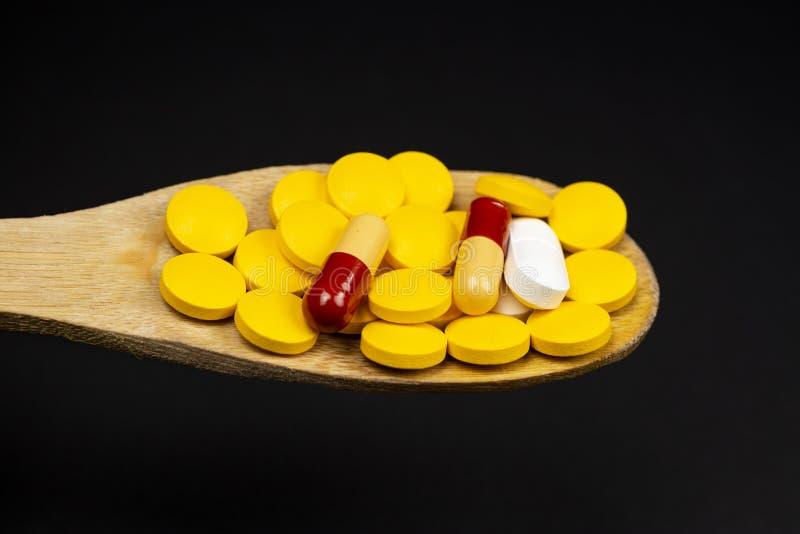 Pharmazeutische Medizinpillen, auf hölzernem Löffel auf schwarzem Hintergrund lizenzfreie stockfotos