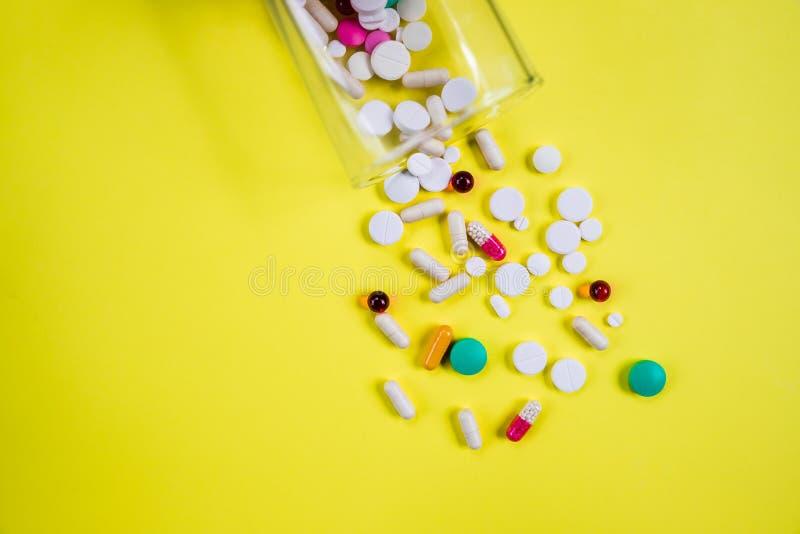 Pharmazeutische Pillenmedizin, Multivitamin und bunte antibiotische Pillenmedizin auf gelbem Hintergrund Tablettenfläschchen, Gla lizenzfreies stockfoto