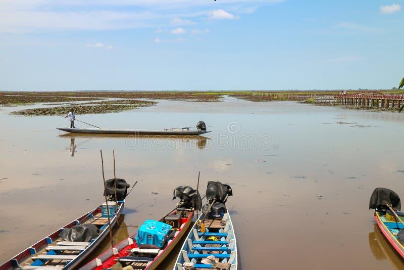 PHATTHALUNG THAILAND - JUNI 18, 2017: Longtail fartygparkering och förbigåfiskare på ett fartyg på Thale Noi Waterbird Park, Phat royaltyfri foto