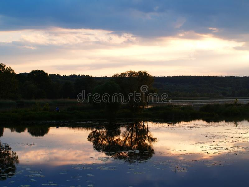 Phenomenal sunset. Over the lake Pasternik with a beautiful sun piercing through the clouds and reflecting off the surface of the water stock photos