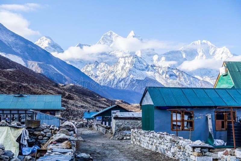 Pheriche, Nepal 04/16/2018: El pequeño pueblo con la nieve hermosa capsuló el fondo de la montaña foto de archivo libre de regalías