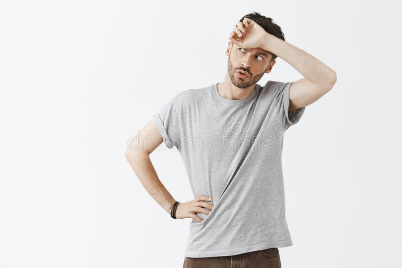 Phew so close. Portrait of relieved handsome dark-haired man with beard in grey t-shirt whiping sweat from forehead stock photo