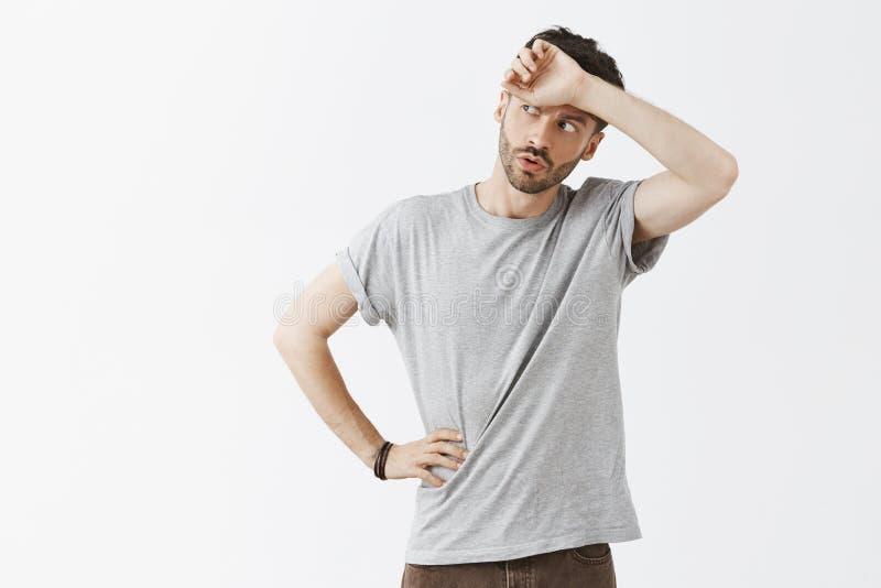 Phew så nära Ståenden av den lättade stiliga mörkhåriga mannen med skägget i den gråa t-skjortan som whiping, svettas från pannan arkivfoto