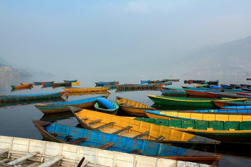 Phewa与雾早晨,尼泊尔的湖岸的五颜六色的小船标志 免版税库存图片