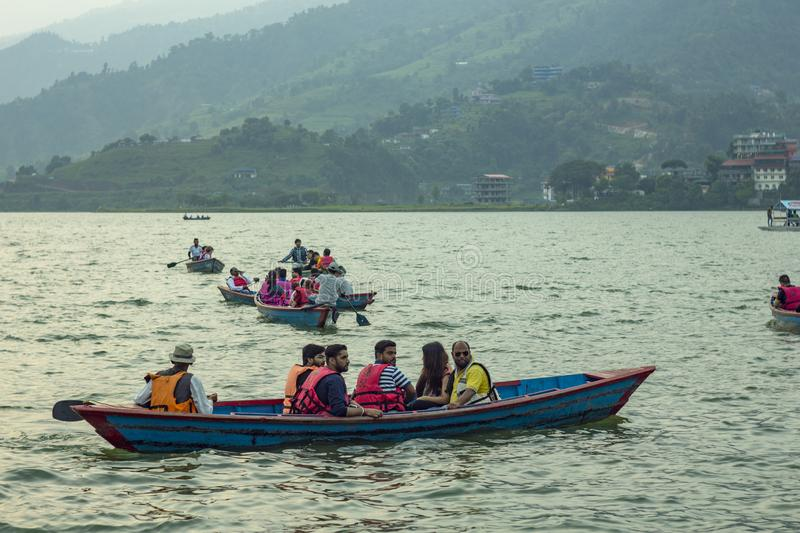 Indian tourists in red life jackets in a rowing boat on a background of green mountains in stock photos
