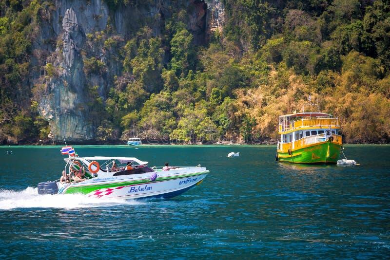 Phi Phi ö, Thailand - Februari 10, 2019: Lyckliga folkturister som seglar på hastighetsfartyget nära kust av den steniga ön arkivbild