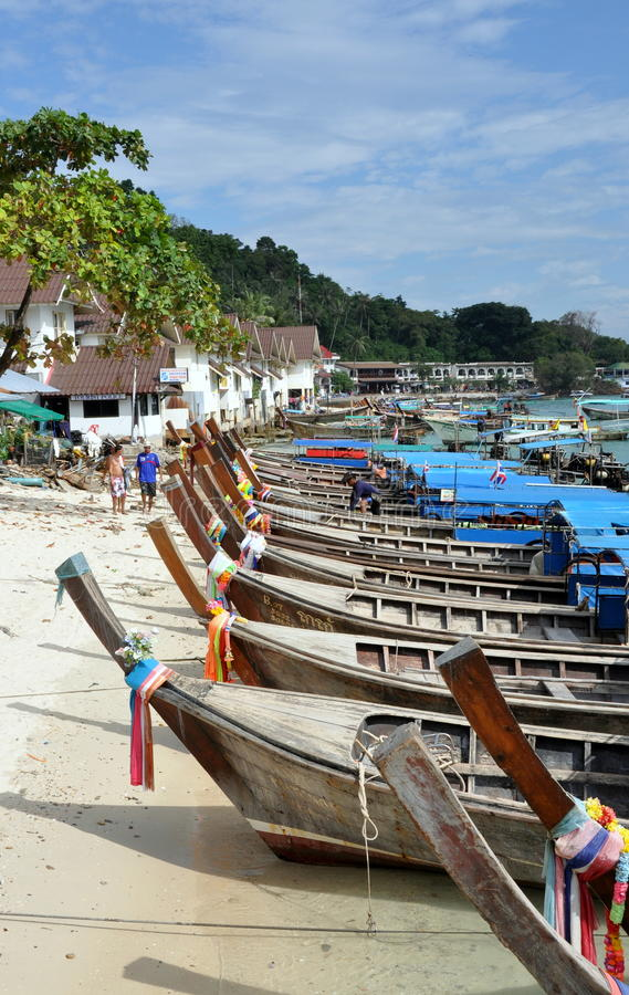 Phi Phi Don Island, Thailand: Long Boats. A row of wooden Thai long boats sit on a beach at Koh Phi Phi Don island a two hour boat ride from Phuket, Thailand stock image