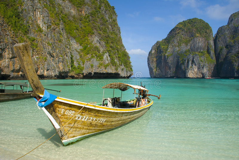 Phi Phi islands beach lagoon. Old fishing boat beached in turquoise water colored bay stock photo