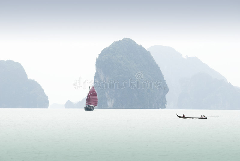 Phi Phi islands with two boats. A junk and fishing boat navigating the islands in Phuket, Thailand royalty free stock images