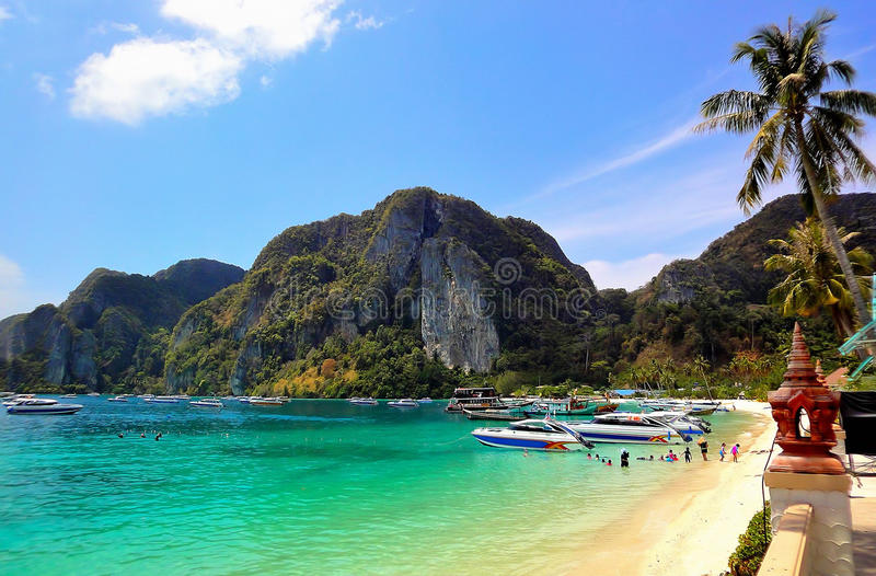 Phi Phi Pier Beach. Speedboats and ferries are docking in front of the beautiful sandy beach of Phi Phi Pier where children are enjoying swimming and snorkeling stock photos