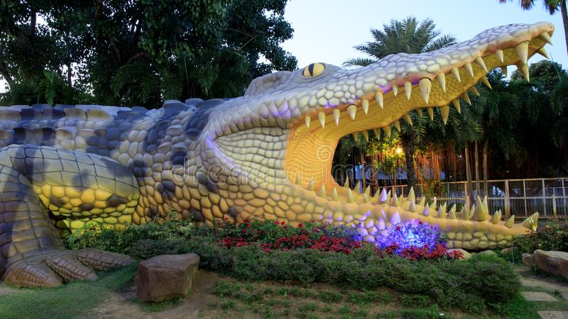 Big crocodile statue at night or evening time in public park of Bueng See Fai, Phichit Province, Thailand. Phichit, Thailand - 2 January 2019 : Big crocodile royalty free stock photo
