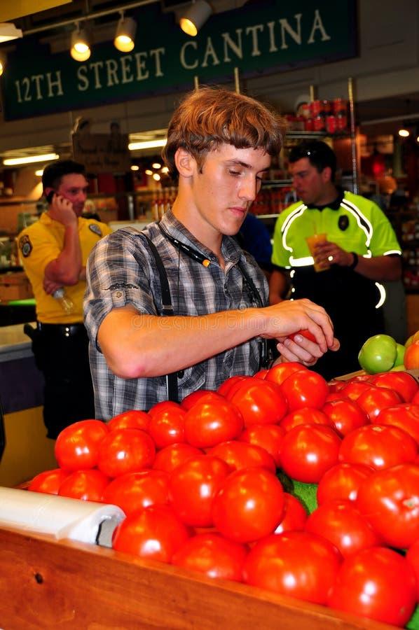 Philadelphia, PA: Young Man Buhying Tomatoes Editorial Stock Image