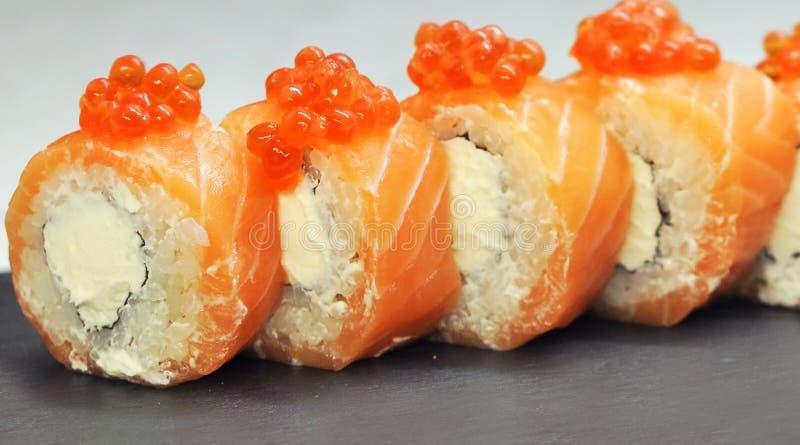 Philadelphia-Rollensushi mit Lachsen, geräucherter Aal, Gurke, Avocado, Frischkäse, roter Kaviar Sushimenü Japanische Nahrung stockbild