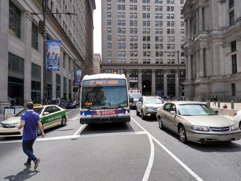 Philadelphia SEPTA Bus To Penn's Landing, Philadelphia, PA, USA. A pedestrian crosses in front of traffic near City Hall, including a taxi and bus number 17 to stock images