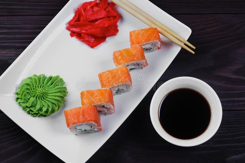 Philadelphia sushirullar på en vit fyrkantig platta med wasabi, soya och ingefäran mörkt trä för bakgrund royaltyfria foton