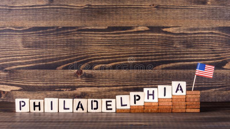 Philadelphia, United States. Politics, economic and immigration concept. Wooden letters and flag on the office desk stock photos