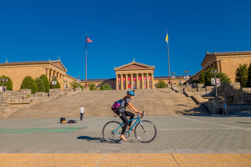 PHILADELPHIA, USA - NOVEMBER 22, 2016: Unidentified woman biking in front of Museum of Art East entrance and North wing royalty free stock photography