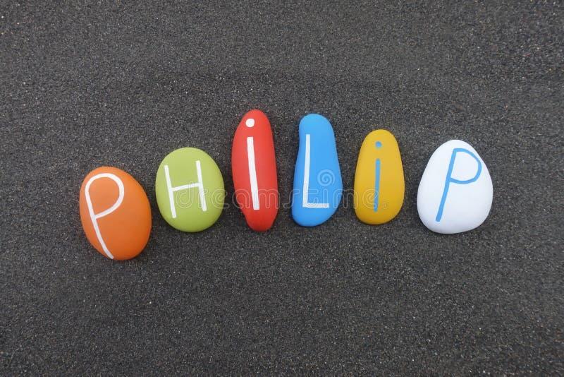 Philip, männlicher Vorname verfasst mit farbigen Steinen über schwarzem vulkanischem Sand stockfotografie