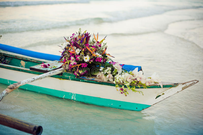 Philippine boat and a bouquet of flowers. Wedding in the tropics concept royalty free stock image