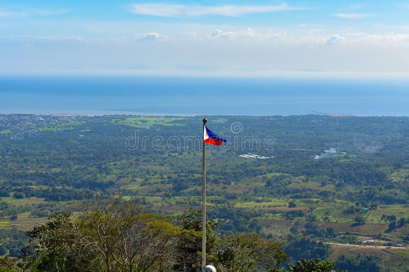 Philippine flag with Bataan Province and Manila Bay in the background. Philippine flag waving with the wind during summer and with the Bataan Province and Manila stock photography