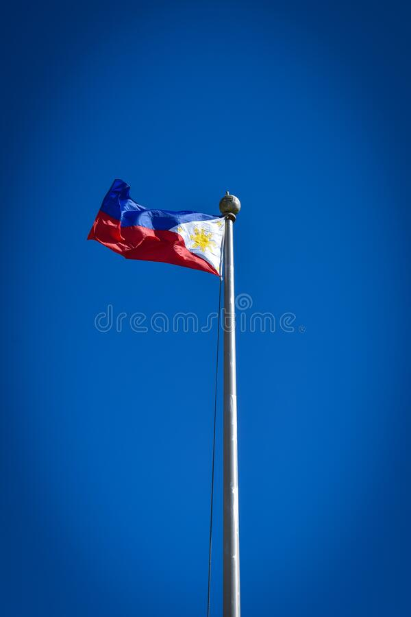 Philippine national flag in blue, red, white and yellow colors. Philippine national flag waving against a clear, blue sky with the blue, red, and white colors stock photo