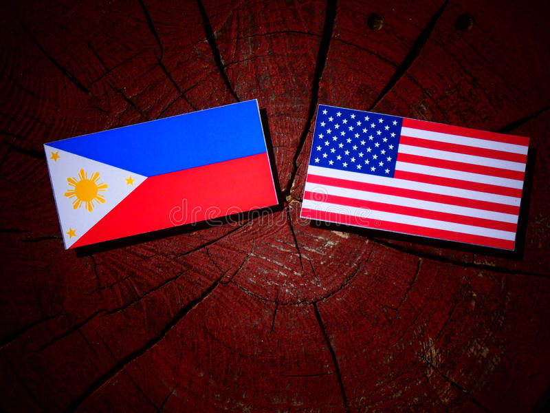 Philippines diminuent avec le drapeau des Etats-Unis sur un tronçon d'arbre photographie stock libre de droits