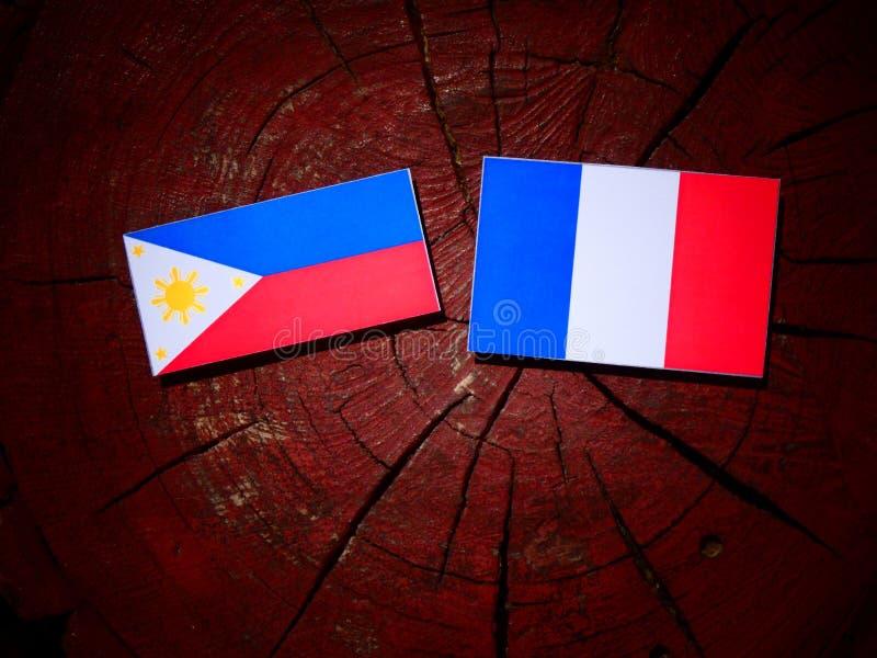 Philippines diminuent avec le drapeau français sur un tronçon d'arbre d'isolement photos stock