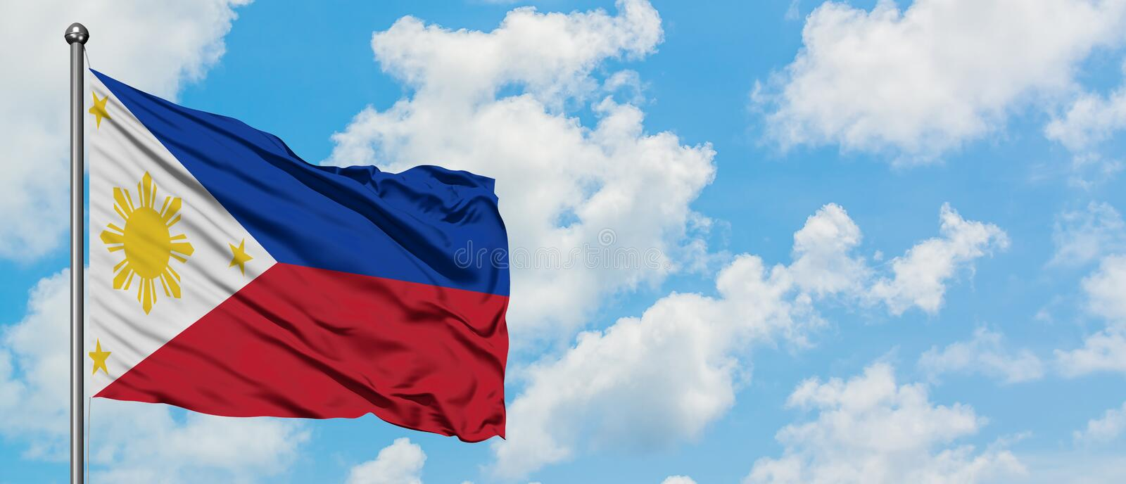 Philippines flag waving in the wind against white cloudy blue sky. Diplomacy concept, international relations.  royalty free stock image