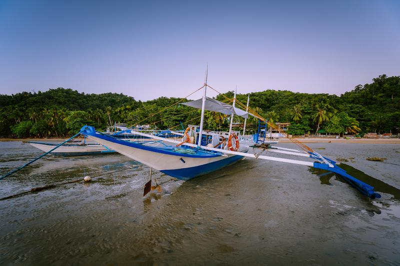 The Philippines`s Banca boat. Traditional fishing boat on beach during low tide in evening light. El Nido,Palawan.  stock images