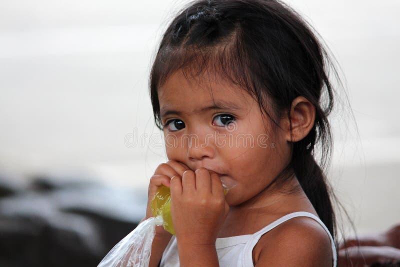 PHILIPPINISCHE KLEINES MÄDCHEN-TRINKENDE LIMONADE von der PLASTIKTASCHE, Philippinen, Bohol-Insel stockfotos
