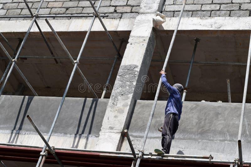 Philippinischer Bauarbeiter, der Metallrohrgestelle auf hohes Gebäude allein ohne Schutzanzug installiert stockfoto