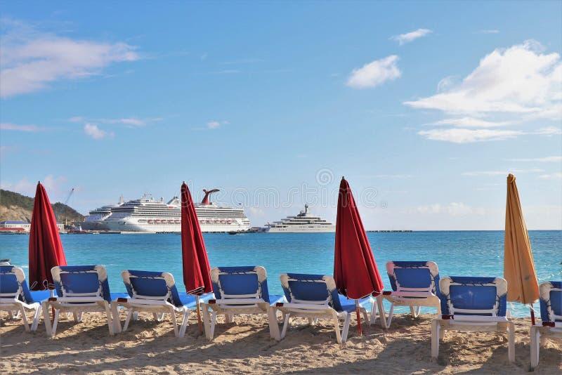 Philipsburg, St Martin - 1/23/18: Ombrelli di spiaggia e sedie di salotto lungo la spiaggia e la nave da crociera di conquista di immagine stock libera da diritti